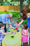 Family Dyes Easter Eggs Outside Stock Photo