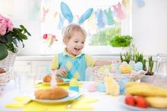 Kids at Easter breakfast. Eggs basket, bunny ears. Stock Image