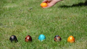 Family Easter game with painted colorful eggs on grass. Stock Photos