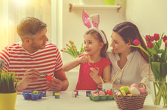 Family easter at home. Family coloring eggs for easter holiday at home on table stock image