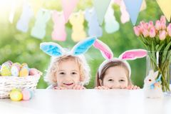 Kids with bunny ears and eggs on Easter egg hunt. Family Easter morning. Children dye eggs. Kids with bunny ears search for candy and chocolate eggs on Easter Royalty Free Stock Photos