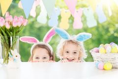 Kids with bunny ears and eggs on Easter egg hunt. Family Easter morning. Children dye eggs. Kids with bunny ears search for candy and chocolate eggs on Easter stock photo