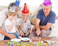 Family eating the birthday cake together. At home stock image