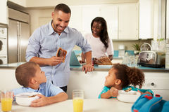 Family Eating Breakfast At Home Together. With Children Sitting At Table Smiling At Father Stock Photos