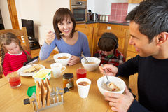 Family Eating Breakfast Whilst Children Play. Family Eating Breakfast Together In Kitchen Whilst Children Play With Gadgets Royalty Free Stock Photo