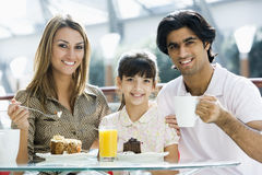 Family eating cake in cafe. Looking to camera royalty free stock photo