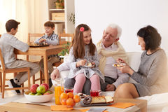 Family eating a cake. Happy family eating a cake in a living room royalty free stock photography