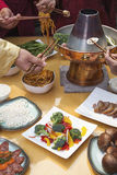Family eating Chinese hot pot, hands only Royalty Free Stock Images