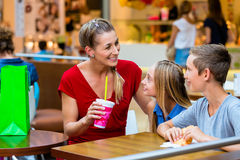 Family eating and drinking in cafe at shopping mall Royalty Free Stock Photography