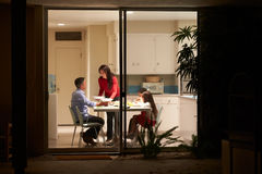 Family Eating Evening Meal Viewed From Outside Stock Photo