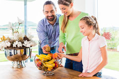 Family eating fresh fruits for healthy living in kitchen. Mother, father, child picking fresh fruits for healthy living in home kitchen royalty free stock photography