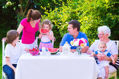 Family eating fruit in the garden. Happy big family - young mother and father with kids, teen age son, cute toddler daughter and a little baby, enjoying lunch royalty free stock image