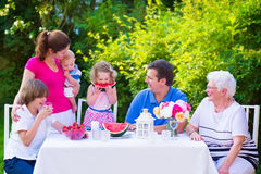 Family eating fruit in the garden. Happy big family - young mother and father with kids, teen age son, cute toddler daughter and a little baby, enjoying lunch stock image