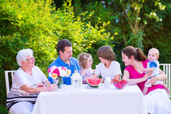 Family eating fruit in the garden. Happy big family - young mother and father with kids, teen age son, cute toddler daughter and a little baby, enjoying lunch royalty free stock photos