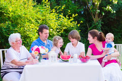Family eating fruit in the garden. Happy big family - young mother and father with kids, teen age son, cute toddler daughter and a little baby, enjoying lunch stock photos