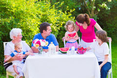 Family eating fruit in the garden. Happy big family - young mother and father with kids, teen age son, cute toddler daughter and a little baby, enjoying lunch stock photo