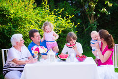 Family eating fruit in the garden Royalty Free Stock Image