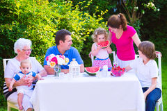 Family eating fruit in the garden. Happy big family - young mother and father with kids, teen age son, cute toddler daughter and a little baby, enjoying lunch royalty free stock images