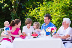 Family eating fruit in the garden. Happy big family - young mother and father with kids, teen age son, cute toddler daughter and a little baby, enjoying lunch stock photography