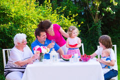 Family eating fruit in the garden. Happy big family - young mother and father with kids, teen age son, cute toddler daughter and a little baby, enjoying lunch royalty free stock photo