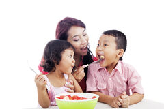 Family eating Fruit Salad. Asian young mother and children eating healthy snack - fruit salad Stock Photos