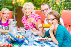 Family at eating in garden barbecue royalty free stock image