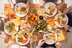 Family eating healthy meal. Top view of family eating healthy meal beside table royalty free stock photos