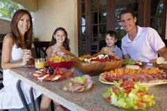 Family Eating Healthy Salad and Food Meal. An attractive happy, smiling family of mother, father, son and daughter eating healthy food with ham, cheese and fresh stock photography