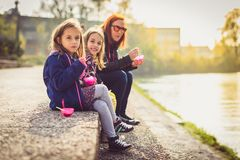 Family eating ice cream, sitting on banks of river Ljubljanica. Mother and twin daughters are sitting next to a river, eating dessert with river and sun in the Stock Images
