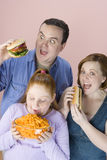 Family Eating Junk Food. Obese family eating junk food isolated over pink background stock photos