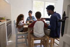 Family eating at kitchen table, back view, seen from doorway Stock Photography