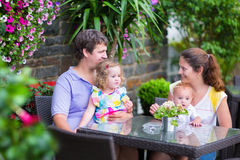 Family eating lunch in outdoor cafe. Happy young family, parents with two children, adorable little girl and a funny baby boy, eating lunch in a beautiful Stock Photography