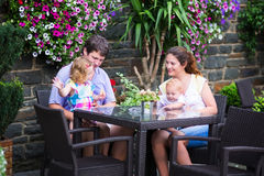 Family eating lunch in outdoor cafe. Happy young family, parents with two children, adorable little girl and a funny baby boy, eating lunch in a beautiful Stock Photo