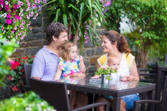Family eating lunch in outdoor cafe. Happy young family, parents with two children, adorable little girl and a funny baby boy, eating lunch in a beautiful Royalty Free Stock Photos