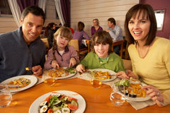 Family Eating Lunch Together In Restaurant. Smiling at camera Stock Photo