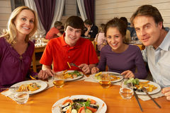 Family Eating Lunch Together In Restaurant. Smiling at camera Stock Images