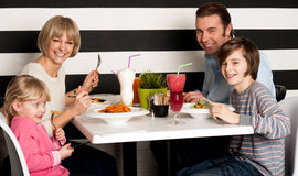 Family eating lunch together in restaurant. Father and mother with children enjoying meal in restaurant Royalty Free Stock Image