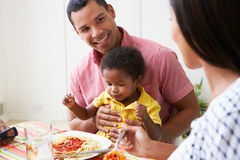 Family Eating Meal Together At Home. Smiling To Each Other Stock Images
