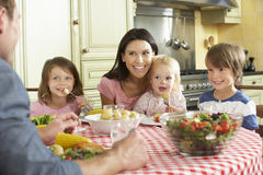Family Eating Meal Together In Kitchen Royalty Free Stock Image