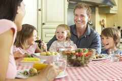 Family Eating Meal Together In Kitchen Stock Photography