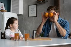 Family, eating and people concept - happy father and daughter having breakfast at home. Making a fresh organic orange juice together stock photography