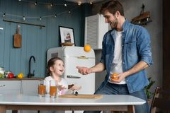 Family, eating and people concept - happy father and daughter having breakfast at home. Making a fresh organic orange juice together stock photos
