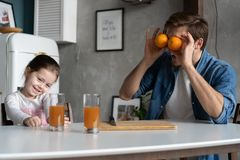 Family, eating and people concept - happy father and daughter having breakfast at home. Making a fresh organic orange juice together royalty free stock photography