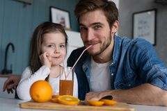 Family, eating and people concept - happy father and daughter having breakfast at home. Making a fresh organic orange juice together stock images