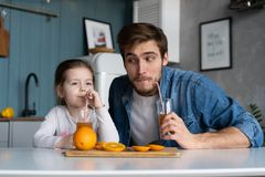Family, eating and people concept - happy father and daughter having breakfast at home. Making a fresh organic orange juice together royalty free stock images