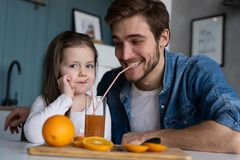 Family, eating and people concept - happy father and daughter having breakfast at home. Making a fresh organic orange juice together royalty free stock photo