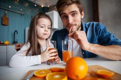 Family, eating and people concept - happy father and daughter having breakfast at home. Making a fresh organic orange juice together royalty free stock image