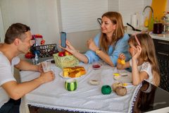 Family, eating and people concept - happy mother, father and daughter having breakfast at home. stock photo