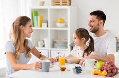 Happy family having breakfast at home. Family, eating and people concept - happy mother, father and daughter having breakfast at home Stock Image