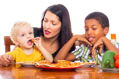 Family eating pizza. Young mother with children eating pizza, isolated on white background Stock Photography